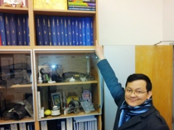 Kartpan adding his final bound thesis to the shelf in James' office.
