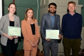 Megan (left) and Hudair (2nd from right) collecting their poster prizes